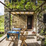 Terraza de madera cubierta con una parra y equipada con mesas y un banco para descansar mirando el jardin