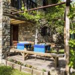 Terraza de madera de Casa Marina con mesas y banco para descansar mirando el jardin
